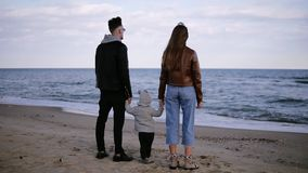 Beautiful, slow motion scene of young, fashioned couple with their child standing in front the sea and looking on stock footage