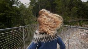 Young woman explores epic hanging bridge stock video