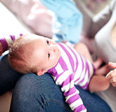 Beautiful small baby on its mothers lap Royalty Free Stock Photography