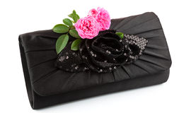 Beautiful small black clutch with fresh pink twig of flower rose. Isolated on white background Stock Photos