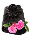 Beautiful small black clutch with fresh pink twig of flower rose Stock Photography