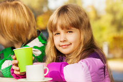Beautiful small blond girl with green cup Stock Image