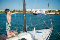 Beautiful small boy wearing sunglasses and shorts pointing his finger at distance standing aboard recreational boat Stock Photo