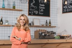 beautiful small business owner smiling at camera while standing stock image
