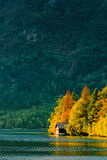 Beautiful small cottage house at Bohinj lake in Slovenia. N national park Triglav in autumn sunset Royalty Free Stock Photography