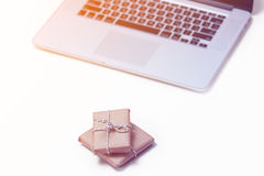 Beautiful small gifts and cool laptop on the wonderful pink back Royalty Free Stock Photos