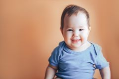 Beautiful small girl or boy with dark hair smiling on a bright orange background colour of 2019 with space for text happy smile. Look at camera royalty free stock image