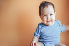 Beautiful small girl or boy with dark hair smiling on a bright orange background colour of 2019 with space for text happy smile. Look at camera royalty free stock photography