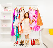 Beautiful small girl choosing clothes in the shop Stock Photos