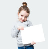 Beautiful small girl. A girl coyly flirtatiously looking at the camera. Embarrassing. Holding white banner for your text advertising information. Gray background Royalty Free Stock Photos