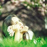 Little girl on grass in bloom. Beautiful small girl with dreaming face lying on green grass in spring pink flower bloom royalty free stock photo