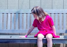 Child talking to a buttefly. Beautiful small girl has a conversation with a tiny little butterfly that decided to sit down beside her on a wood park bench Royalty Free Stock Image