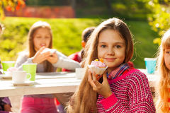 Beautiful small girl holding cupcake and friends Royalty Free Stock Photos