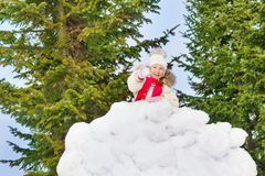 Beautiful small girl holds snowball in the forest Stock Image