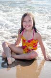 Beautiful little girl  enjoying a sunny day on the beach. Beautiful small girl with a large smiles poses as she enjoys a sunny summers day on the beach Royalty Free Stock Photography