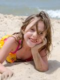 Sandy little girl poses as the wind blows hair into her face. Beautiful small girl with a large smiles poses as she enjoys a sunny summers day on the beach and Royalty Free Stock Images