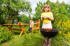 Beautiful small girl near grill holding plate Stock Photography