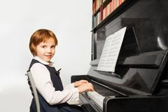 Beautiful small girl in school uniform plays piano Royalty Free Stock Photography