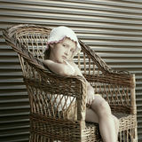 Beautiful small girl seating in wicker chair Royalty Free Stock Images