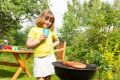 Beautiful small girl stands near grill holding cup Royalty Free Stock Images