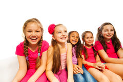Beautiful small girls sit together on white sofa Stock Photography