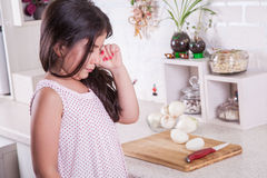 Beautiful small middle eastern girl crying in kitchen, tears of onion. studio shot. Stock Image