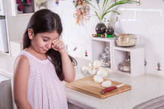 Beautiful small middle eastern girl crying in kitchen, tears of onion. studio shot. Royalty Free Stock Photography