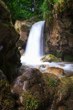 Beautiful small waterfall landscape in the mountains. Beautiful small waterfall landscape in the mountains with lush green bush, rocks and flowing water Stock Photography
