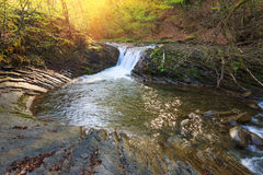 Beautiful small waterfall and rapids on a mountains river in sunlight. Royalty Free Stock Images
