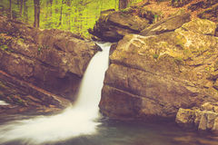 Beautiful small waterfall and rapids on a mountains river in sunlight. Stock Photography