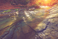 Beautiful small waterfall and rapids on a mountains river in sunlight. Royalty Free Stock Photo