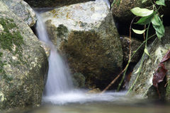 Beautiful small waterfall on a rocky stream Stock Images