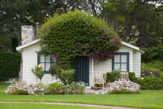 Beautiful small white american house with lots of green and flowers Royalty Free Stock Photo