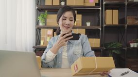 Beautiful smart Asian young entrepreneur business woman owner of SME checking product on stock scan qr code working at home. Small business owner at home stock video footage