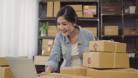 Beautiful smart Asian young entrepreneur business woman owner of SME checking product on stock scan qr code working at home. Small business owner at home stock video