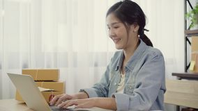 Beautiful smart Asian young entrepreneur business woman owner of SME online checking product on stock and save to computer working
