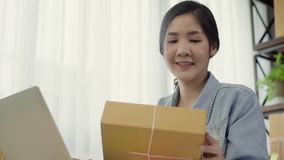 Beautiful smart Asian young entrepreneur business woman owner of SME online checking product on stock and save to computer working. At home. Small business stock footage