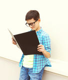 Beautiful smart teenager boy in glasses looking or reading book Royalty Free Stock Photo