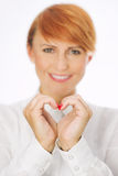 Beautiful smart woman showing symbol of heart with. Beautiful smiling smart woman showing symbol of heart with fingers Royalty Free Stock Image