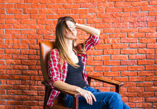 Beautiful smart woman sits on chair near brick wall Royalty Free Stock Photo