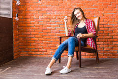 Beautiful smart woman sits on chair near brick wall Royalty Free Stock Photography