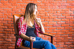 Beautiful smart woman sits on chair near brick wall Stock Image