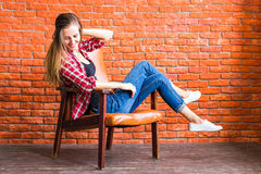 Beautiful smart woman sits on chair near brick wall Royalty Free Stock Photos