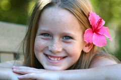 Beautiful smile. A white caucasian kid smiling with a pink flower in her hair Royalty Free Stock Photos
