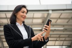 American business woman using smartphone. Beautiful smile American senior business woman, 40 to 50 years old, browsing and playing smart or mobile phone to check Royalty Free Stock Images