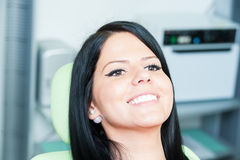 Beautiful smile female patient waiting at dentist. For periodic orthodontic checkup royalty free stock photo