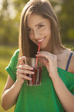 Beautiful smile of a girl holding a glass of juice in her hands. Girl smiling while drinks juice Stock Photography