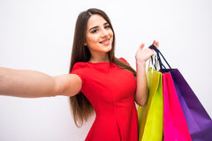 Beautiful smile woman take selfie on phone with color shoping bags in hands on white background. Beautiful smile woman take selfie on phone with color shoping Stock Image