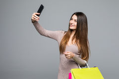 Beautiful smile woman take selfie on phone with color shopping bags in hands on grey. Beautiful smile woman take selfie on phone with color shopping bags in Royalty Free Stock Photos