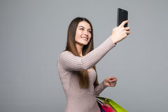 Beautiful smile woman take selfie on phone with color shopping bags in hands on grey. Beautiful smile woman take selfie on phone with color shopping bags in Royalty Free Stock Image